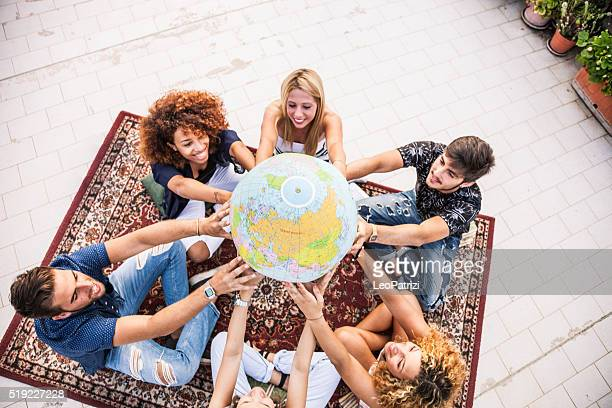 Friends holding and looking an earth globe