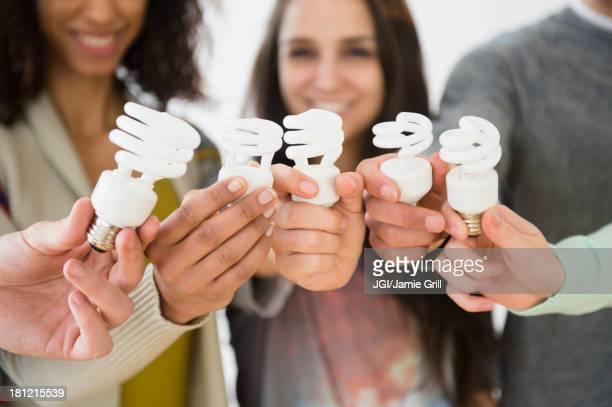 Friends holding fluorescent light bulbs