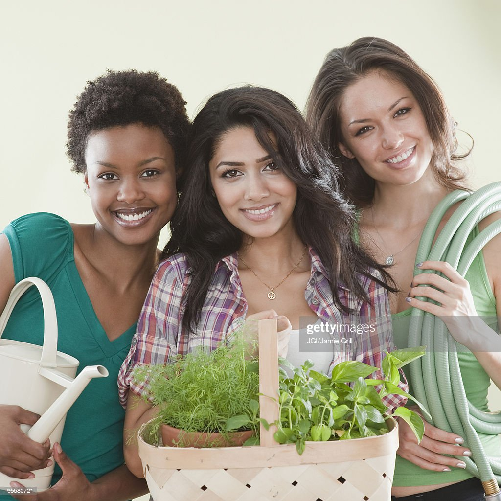 Friends holding gardening supplies : Stock Photo