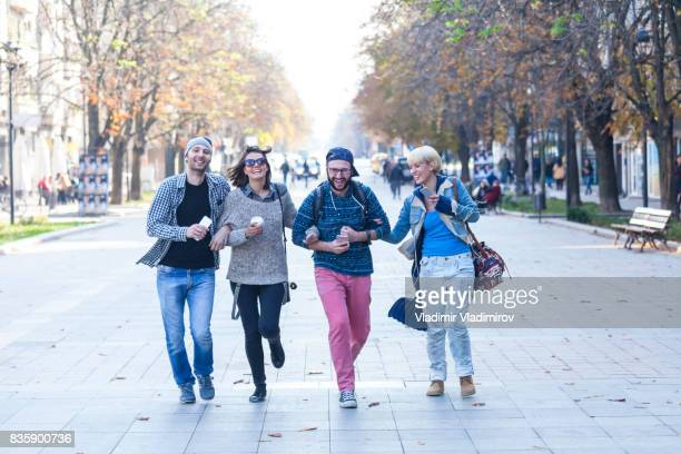 Friends holding hands and hanging out on street