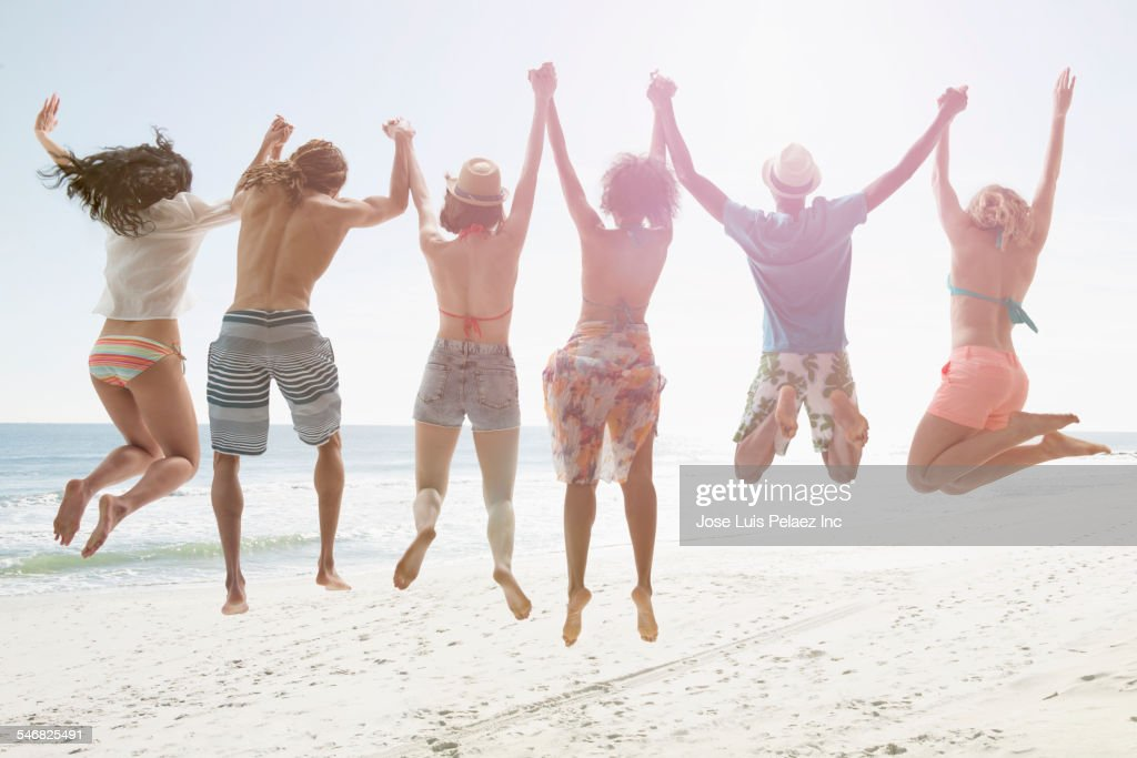 Friends holding hands and jumping for joy on beach