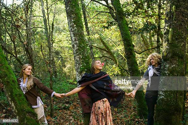 Friends holding hands in woods , Humboldt , California , USA