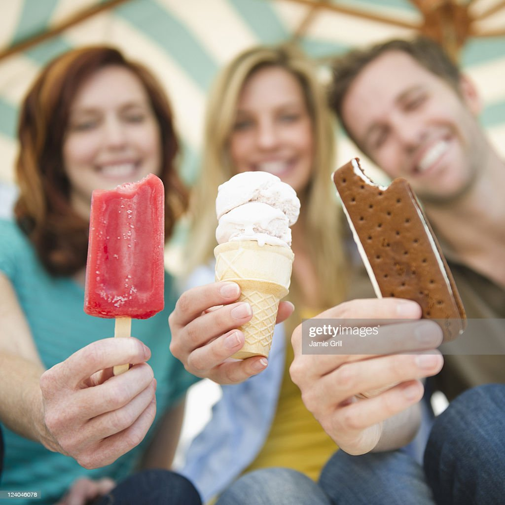 Friends holding out frozen snacks : Stock Photo