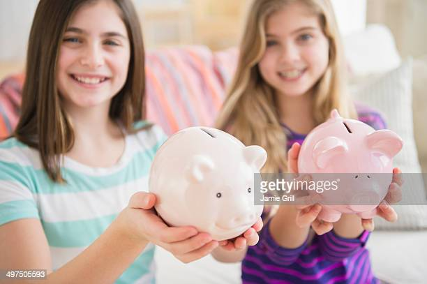 Friends holding piggy banks together