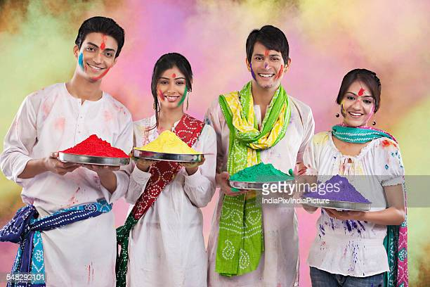 Friends holding trays with colours