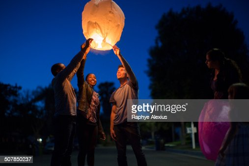 Friends holding up sky lantern to celebrate