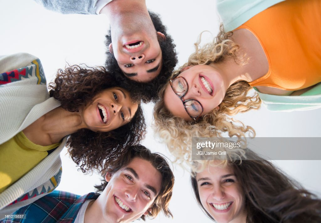 Friends huddled in circle together : Stock Photo