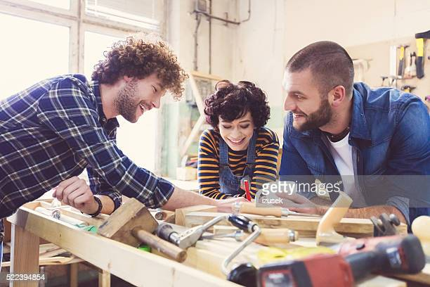 Friends in a construction workshop, learning carpentry