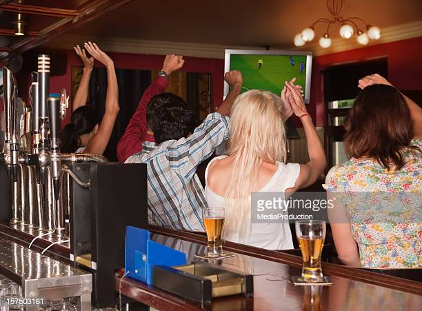 Friends in a pub watching football