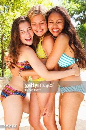Friends in bathing suits hugging : Stock Photo