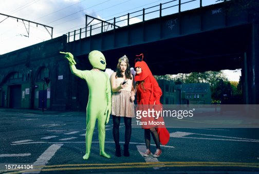 friends in fancy dress checking mobile for map : Stock Photo