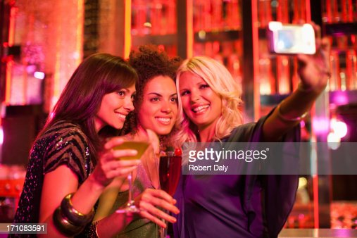 Friends in nightclub taking self-portrait with digital camera