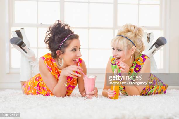 Friends in nostalgic dresses drinking and laying on floor