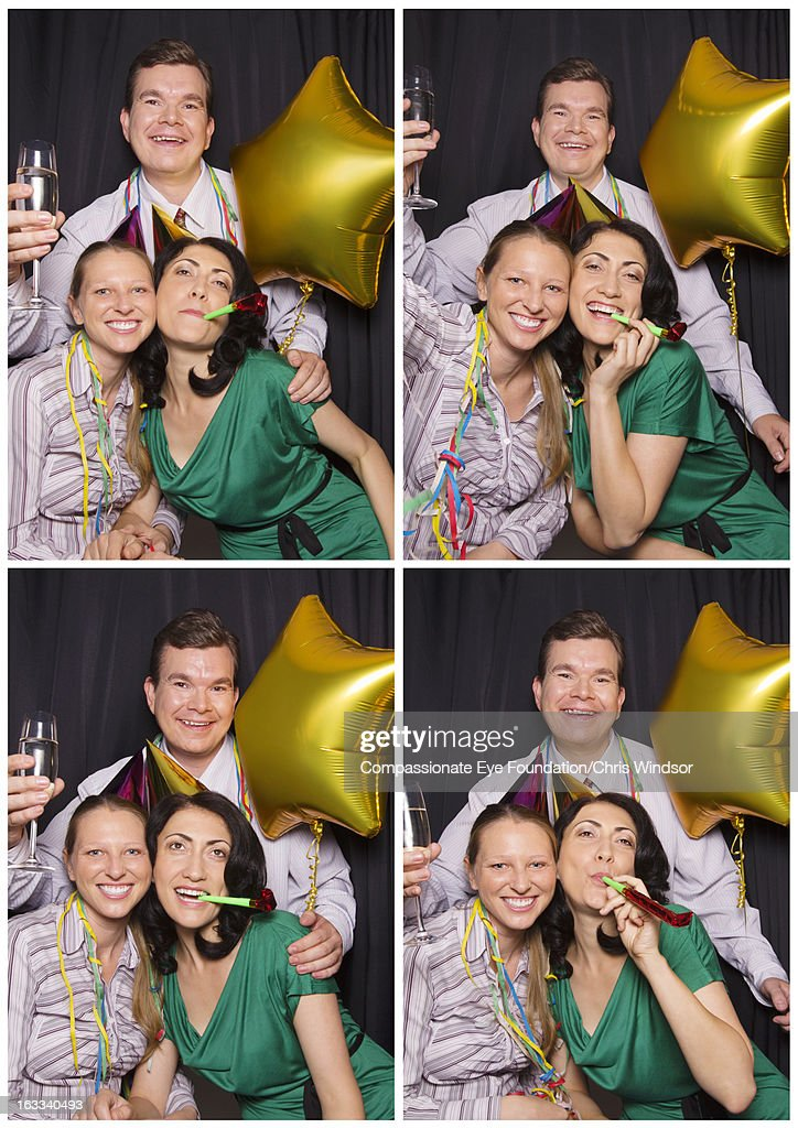 Friends in photo booth with drinks and party hats : Stock Photo