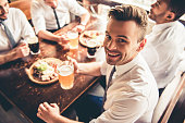 Handsome businessmen are drinking beer, looking at camera and smiling while resting at the pub