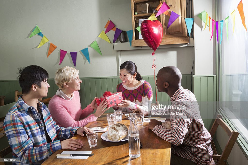 friends in restaurant, woman gets a gift. : Stock Photo
