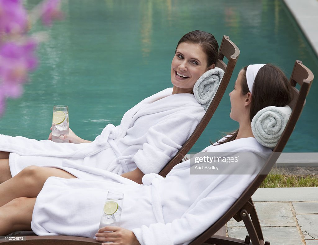 Friends in robes relaxing in lounge chairs at poolside : Stock Photo