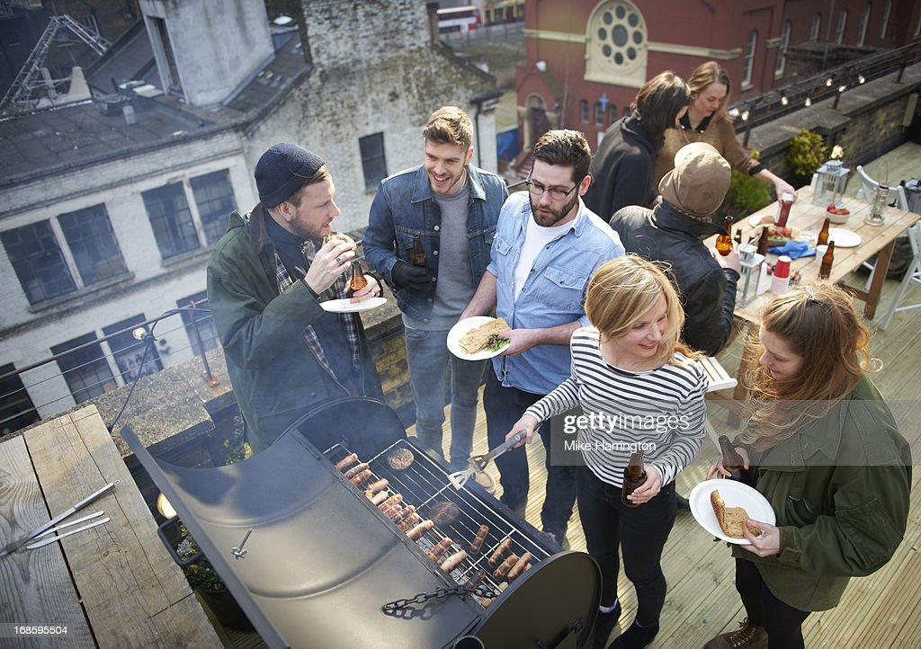 Friends in roof garden sharing barbecued food. : Stock Photo