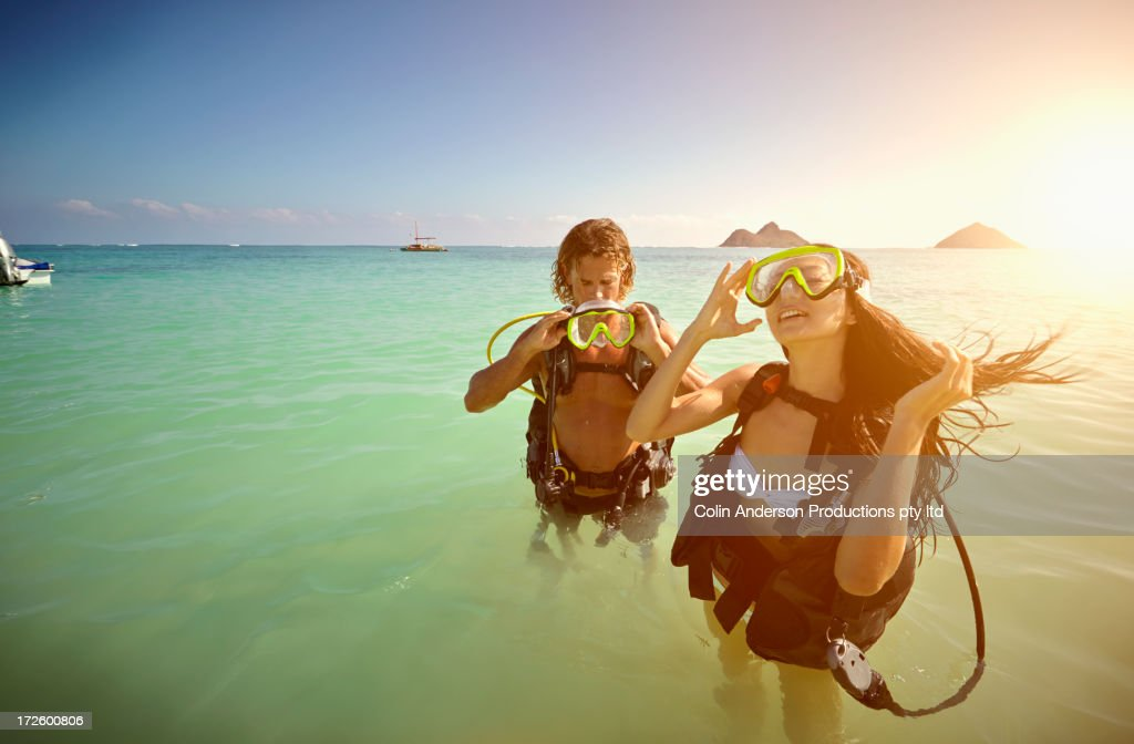 Friends in scuba gear standing in ocean : Stock Photo