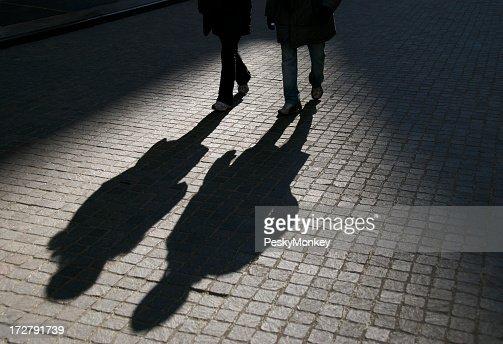 Friends in Shadow Walking on Cobblestone Street