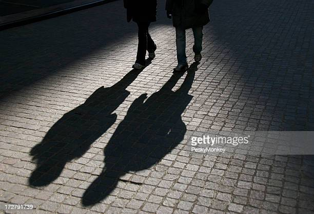 Friends in Shadow Walking on Cobblestone Street