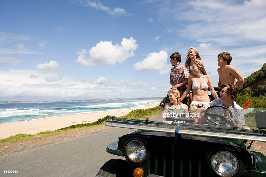Friends in vehicle by the sea