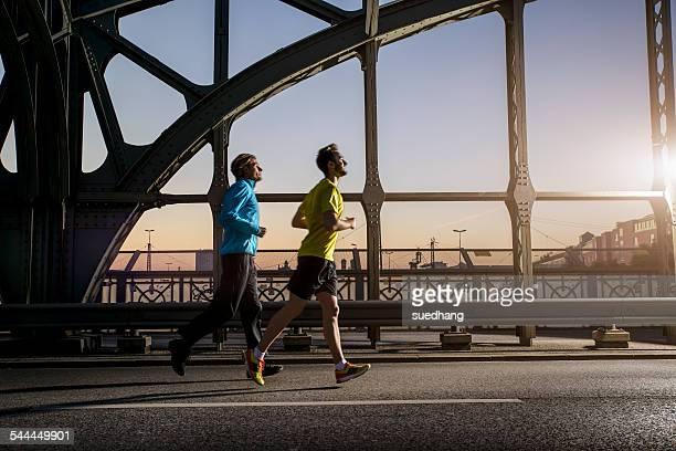 Friends jogging on bridge, Munich, Bavaria, Germany