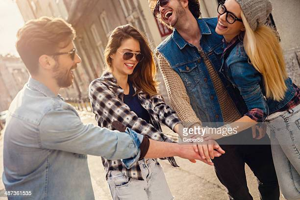 Friends joining hands outdoors