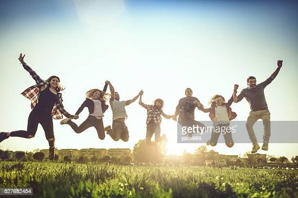 Freunde springen zusammen mit erhöhter Arme