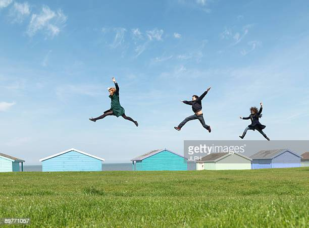 Friends jumping across roofs by seaside