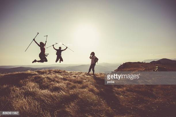 Friends jumping for joy on mountain peak