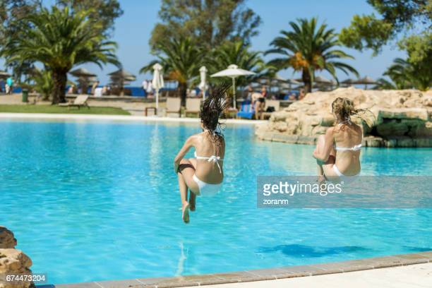 Friends jumping into pool