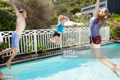 Friends jumping into swimming pool : Stock Photo