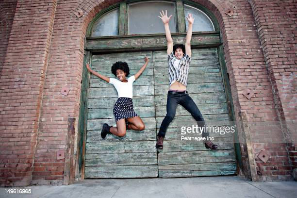 Friends jumping on urban sidewalk