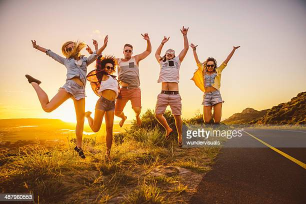 Friends jumping while the sun sets