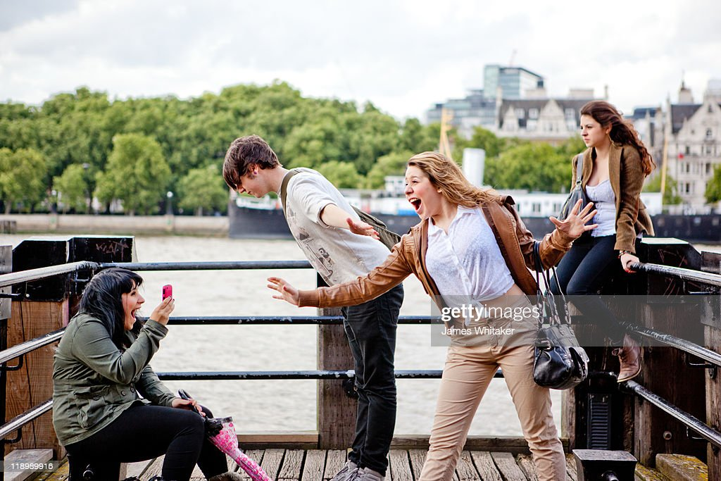 Friends lark around on a pier : Stock Photo