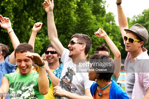 Friends laughing and cheering in the park : Stock Photo
