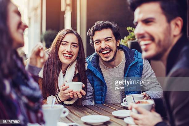 Friends laughing and drinking tea and coffee