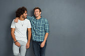 Two friends in casual wear standing and laughing together. Best friends enjoying isolated over grey background. Two men having fun isolated over grey wall with copy space.