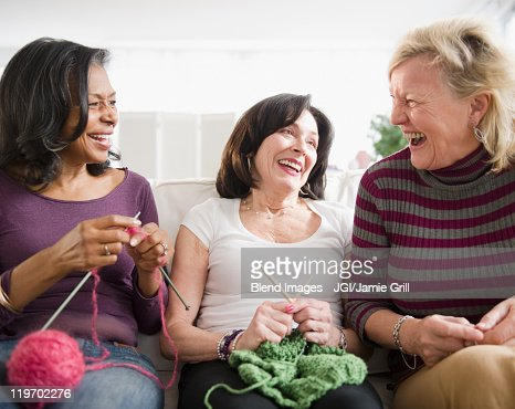 Friends laughing and knitting together