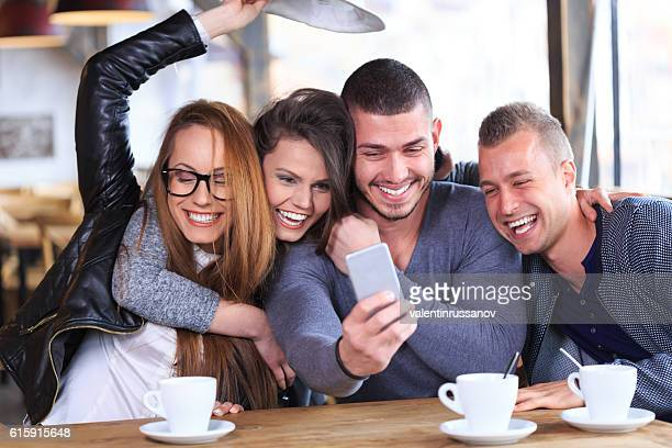 Friends laughing and taking selfie in cafe