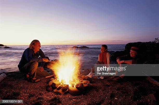 Friends laughing around campfire