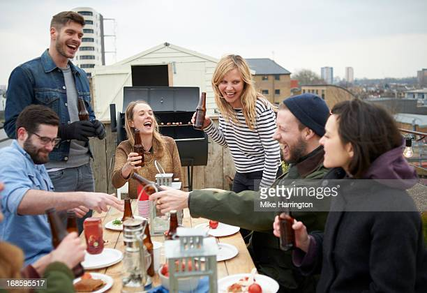 Friends laughing around table in roof garden.