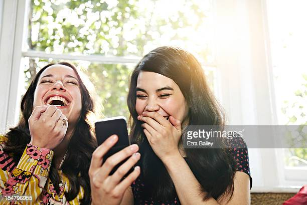 Friends laughing at a mobile phone