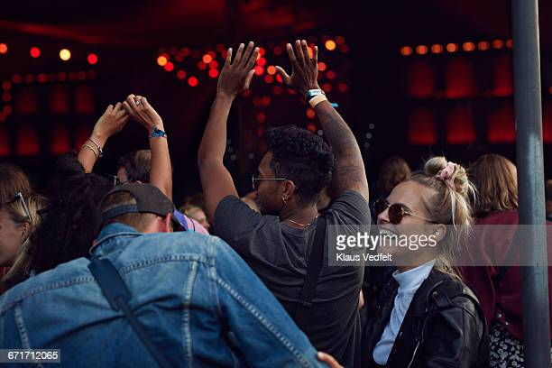 Friends laughing at concert, arms in air