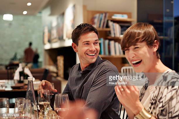 Friends laughing at dinner
