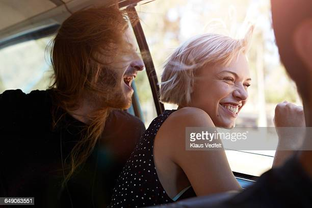 Friends laughing & looking out of window of car