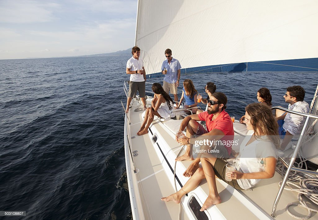 Friends laughing & relaxing on sailboat at sea