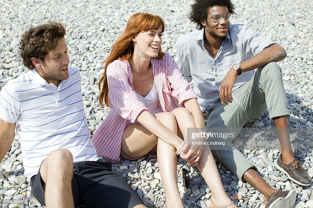 Friends laughing talking on stoney beach. : Stock Photo