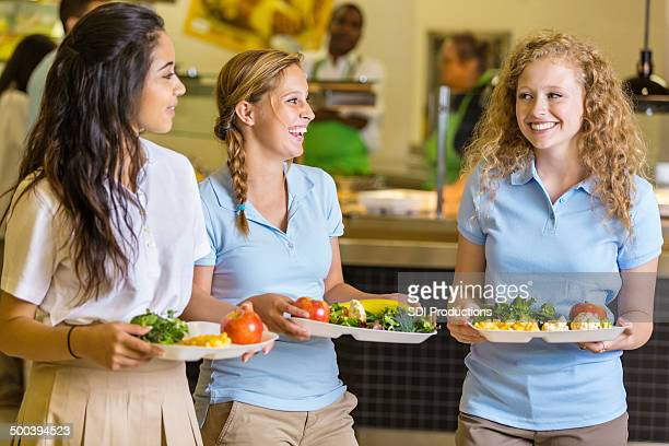 Friends laughing together after purchasing school cafeteria food